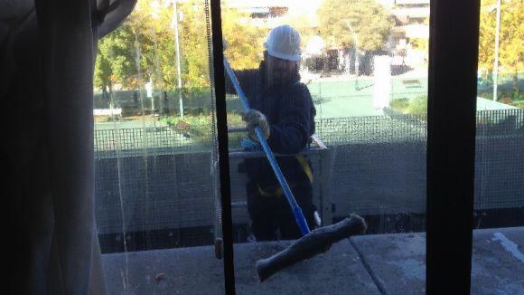 Un treballador neteja la façana de vidre de l'Ajuntament