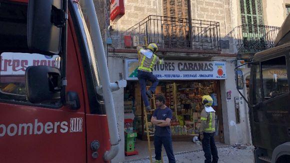 Els Bombers sanegen la façana del balcó de Pintures Cabanas per un lleu despreniment