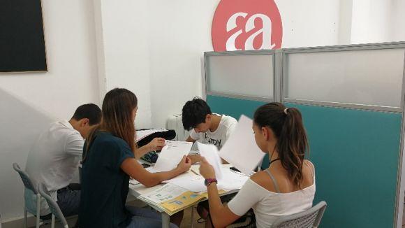 Tres estudiants fent repàs amb una de les impulsores del projecte
