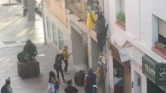 Un grup de persones retira llaços grocs de la via pública