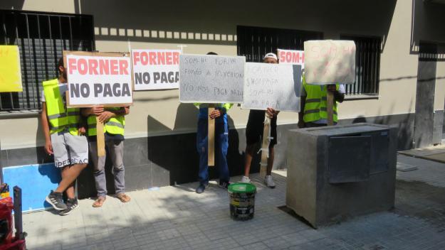 Els treballadors protesten amb pancartes i cartells davant l'immoble / Foto: Cugat Mèdia