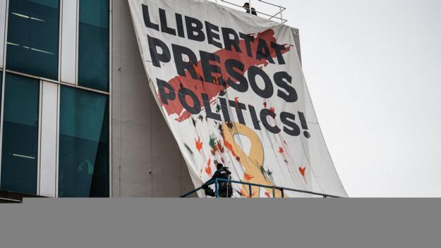 Moment de la col·locació de la pancarta / Foto: Guillem Babitsch