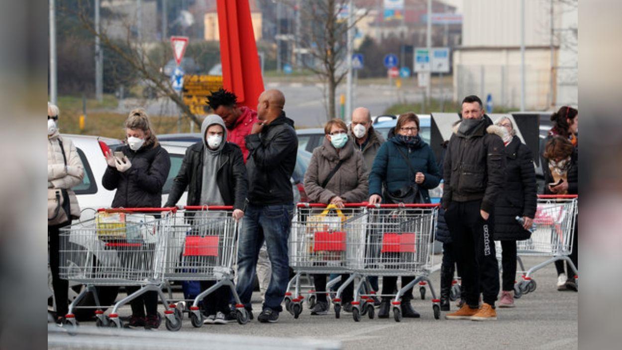 Diverses persones fent cua amb mascaretes a l'exterior d'un supermercat a Itàlia, el 23 de febrer del 2020 / Foto: ACN