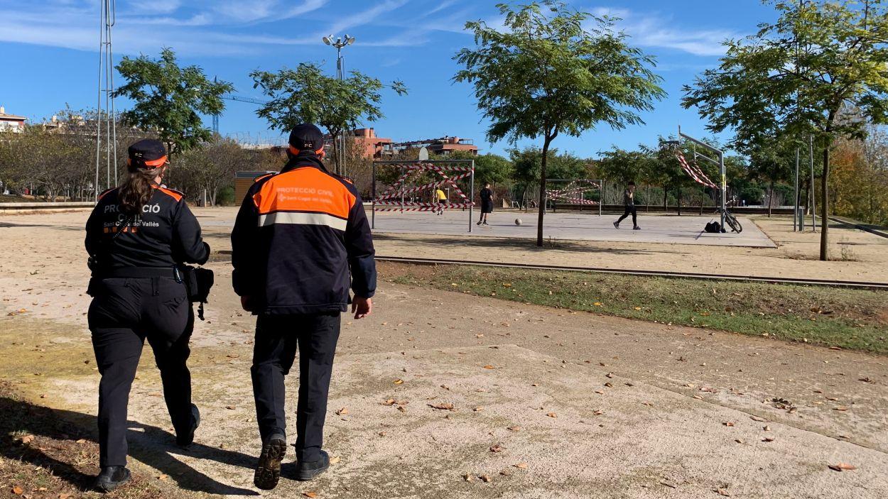 Uns joves utilitzen la pista de bàsquet precintada / Foto: Cugat Mèdia