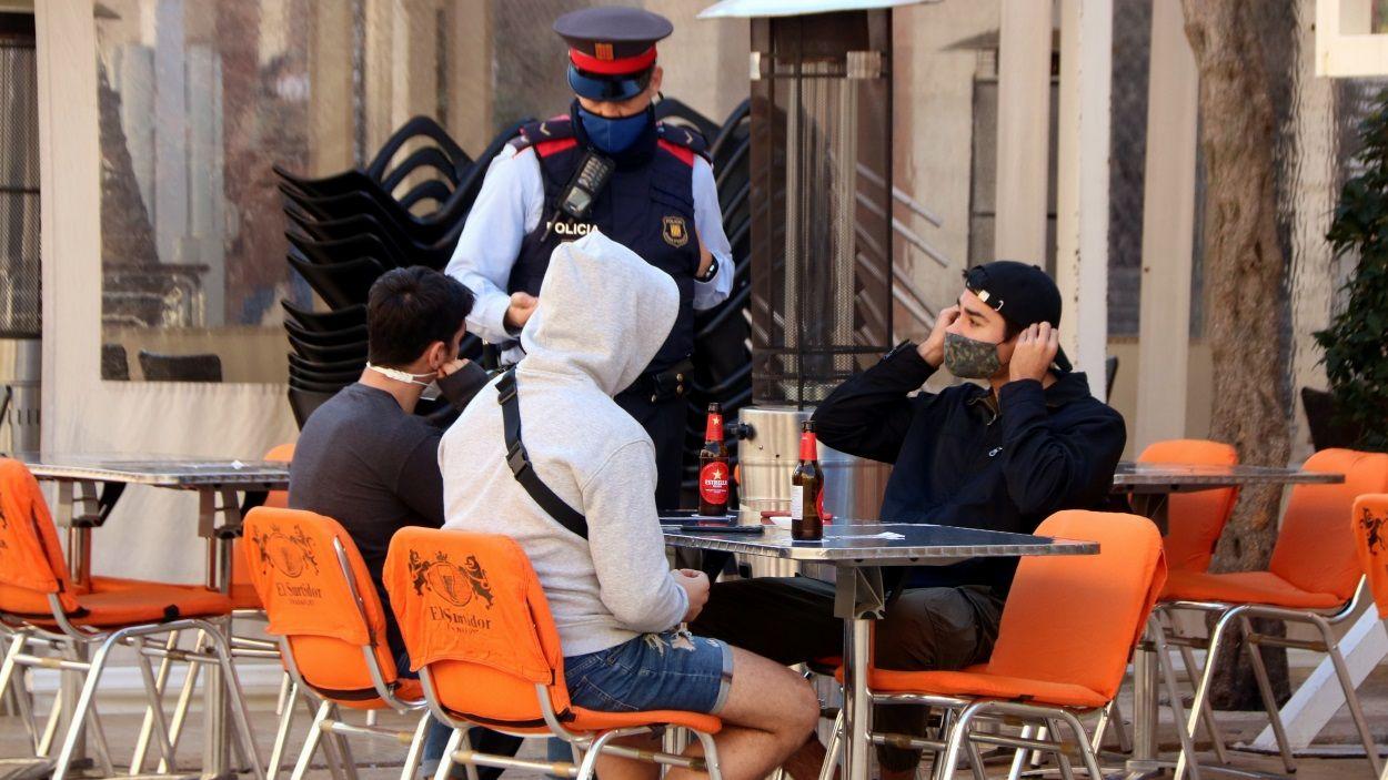 Un agent dels Mossos adverteix uns clients d'una terrassa d'un bar / Foto: ACN