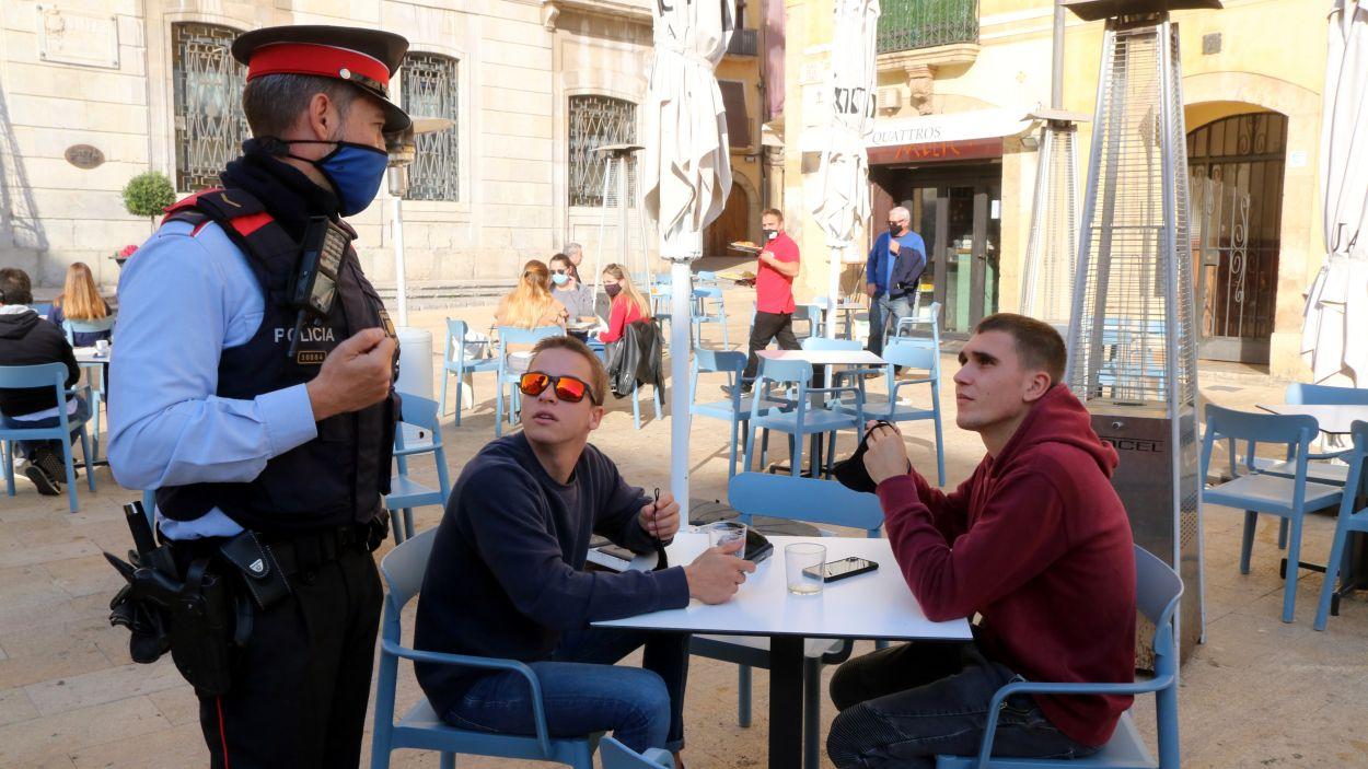 Un agent dels Mossos parla amb dos nois a la terrassa d'un bar de Tarragona / Foto: ACN