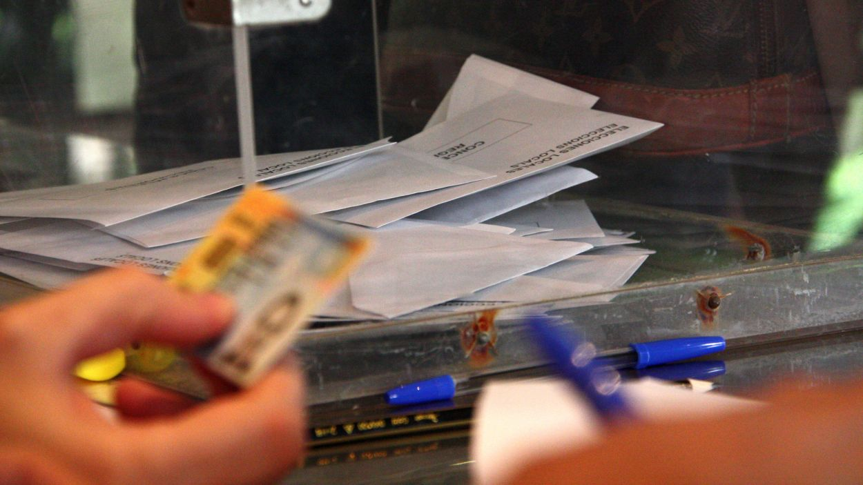 Foto d'arxiu d'una urna i una mà que comprova el DNI per poder votar / Foto: ACN