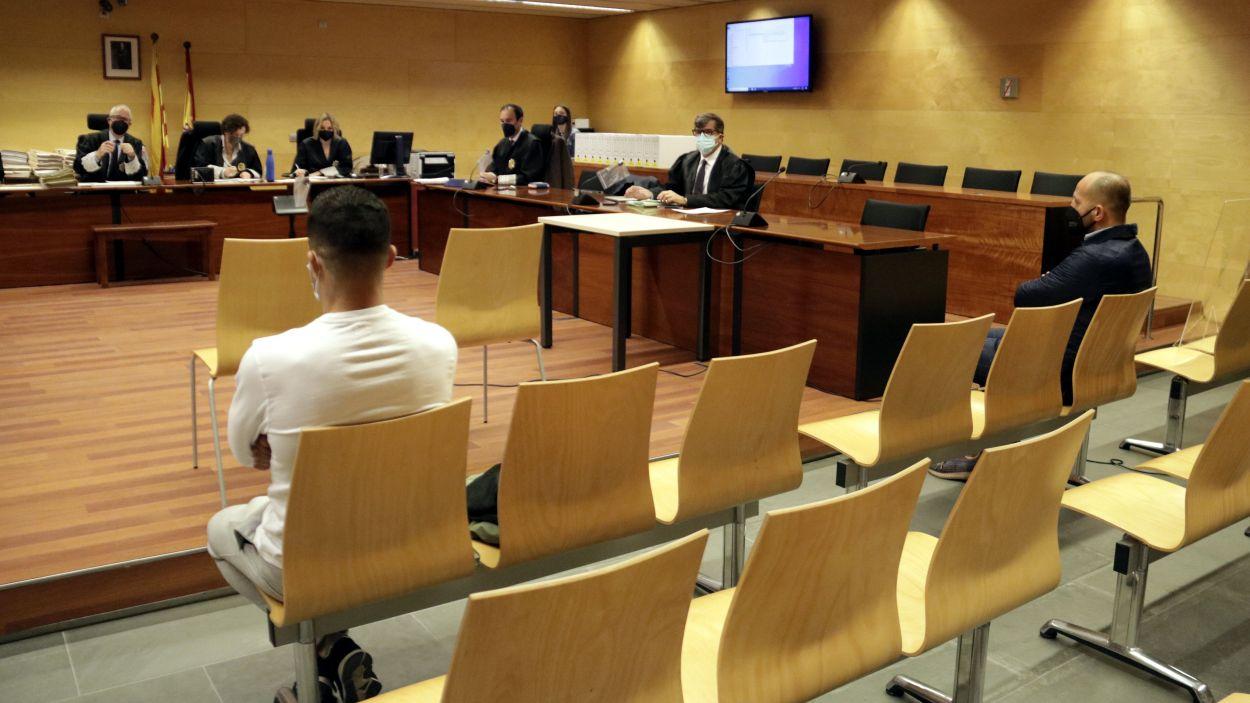 D'esquenes, els dos acusats pel robatori a casa de l'empresari de Platja d'Aro. Foto del primer dia de judici, el 3 de maig del 2021 / Foto: ACN