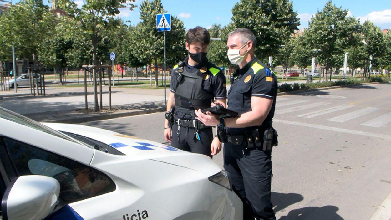 Dos agents de la Policia Local utilitzant una de les tauletes / Foto: Cugat Mèdia
