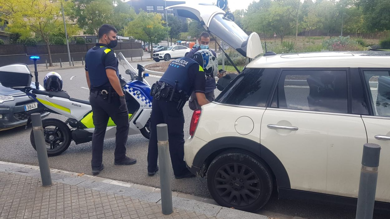 Dos agents de la Policia Local observant el cotxe robat / Foto: Policia Local