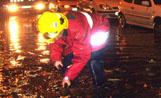 Un bomber intenta desatascar una de les entrades del clavegueram del carrer Sant Jordi, que va quedar inundat d'aigua