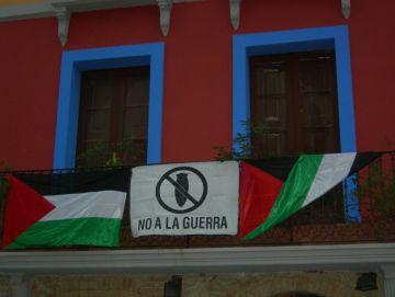 L'Ateneu diu 'No a la guerra' penjant dues banderes de Palestina al balcó