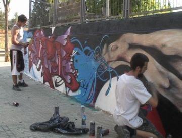 Dos artistes pinten un grafit, amb autorització, al Casal de Joves TorreBlanca