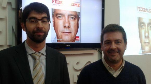 D'esquerra a dreta, David Gutiérrez i Michael Cáceres, amb el cartell de Pere Navarro