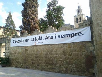 La pancarta a favor de la immersió, a la muralla del Monestir