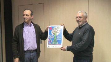 Els organitzadors, amb el cartell promocional de la cursa
