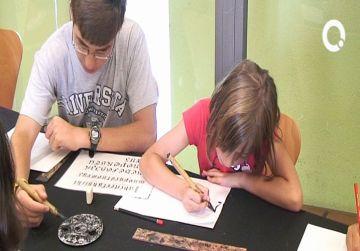 Una desena d'infants aprenen la tècnica de l'escriptura medieval
