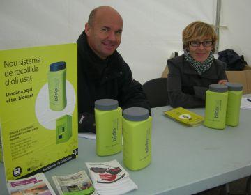 Una taula informativa reparteix bidonets per reciclar l'oli de cuina a la plaça dels Quatre Cantons